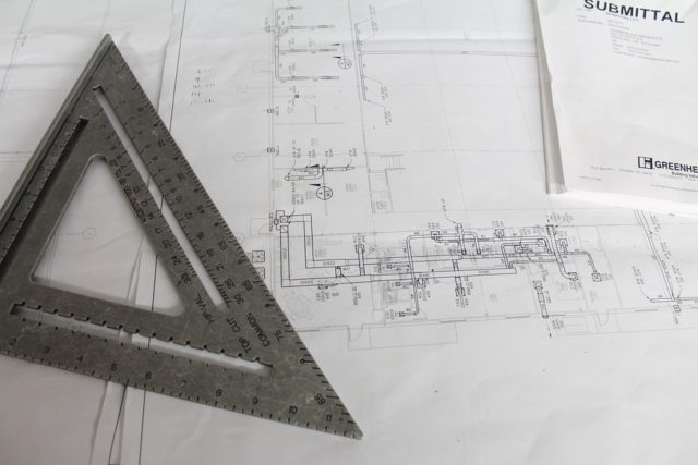 metal set square on a construction blueprint